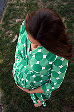 Pregnant woman in green polka dot maternity dress.